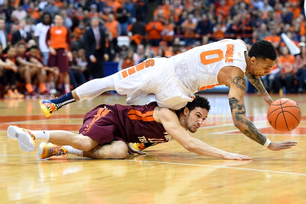 Virginia Tech Hokies guard Devin Wilson (11) and Syracuse Orange forward Michael Gbinije (0) battle for a loose ball during the first half at the Carrier Dome.