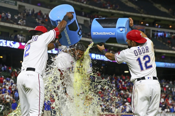 Texas Rangers first baseman Hanser Alberto (2) and second baseman Rougned Odor (12) pour gumballs and powerade on shortstop Elvis Andrus (middle) after the game against the New York Yankees  at Globe Life Park in Arlington.
