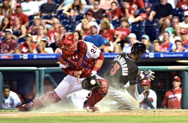 Miami Marlins shortstop Adeiny Hechavarria (3) slides safely into home as Philadelphia Phillies catcher Cameron Rupp (29) handles a late throw during the tenth inning at Citizens Bank Park. The Marlins defeated the Phillies 2-1 in 10 innings.