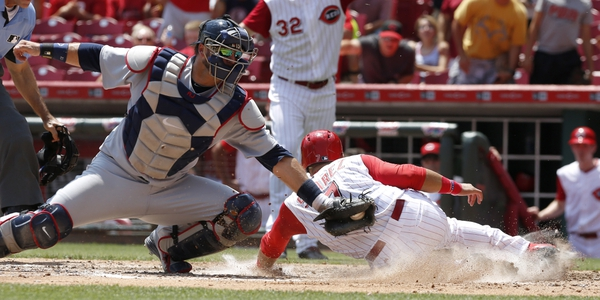 Cincinnati Reds third baseman Eugenio Suarez (7) slides safely into home beating the tag from Atlanta Braves catcher A.J. Pierzynski (15) during the sixth inning at Great American Ball Park.