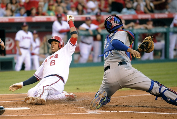 Los Angeles Angels third baseman Yunel Escobar (6) scores a run past Texas Rangers catcher Robinson Chirinos (61) in the first inning at Angel Stadium of Anaheim.