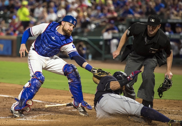 Texas Rangers catcher Jonathan Lucroy (25) tags out Cleveland Indians designated hitter Carlos Santana (41) during the fourth inning at Globe Life Park in Arlington.