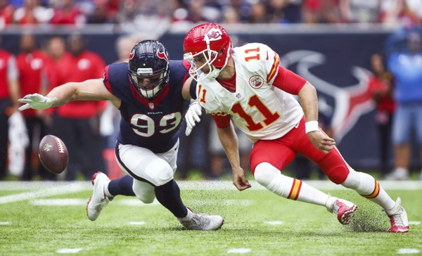 Houston Texans defensive end J.J. Watt (99) and Kansas City Chiefs quarterback Alex Smith (11) attempt to recover a fumble during the first quarter at NRG Stadium.