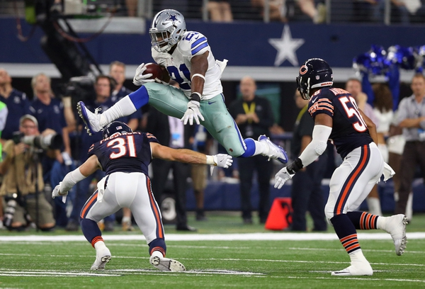 Dallas Cowboys running back Ezekiel Elliott (21) leaps over Chicago Bears safety Chris Prosinski (31) in the fourth quarter at AT&T Stadium.