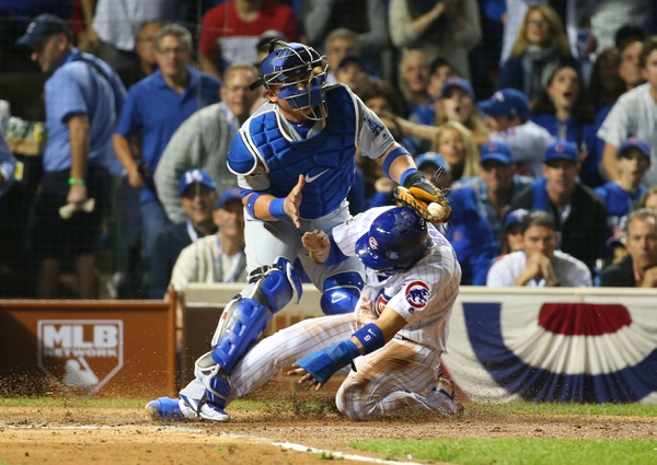 Chicago Cubs infielder Javier Baez (bottom) steals home ahead of the tag by Los Angeles Dodgers catcher Carlos Ruiz (51) during the second inning in game one of the 2016 NLCS playoff baseball series at Wrigley Field.