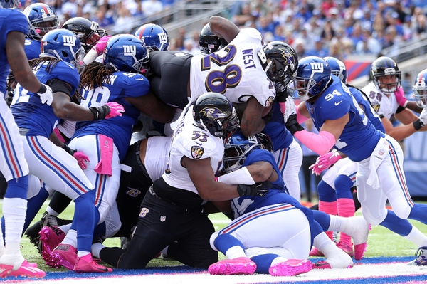 Baltimore Ravens running back Terrance West (28) leaps over the pile for a touchdown against the New York Giants during the first quarter at MetLife Stadium.