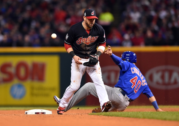 Cleveland Indians second baseman Jason Kipnis (left) commits an error allowing Chicago Cubs catcher Willson Contreras (40) to reach second base in the 7th inning in game two of the 2016 World Series at Progressive Field.