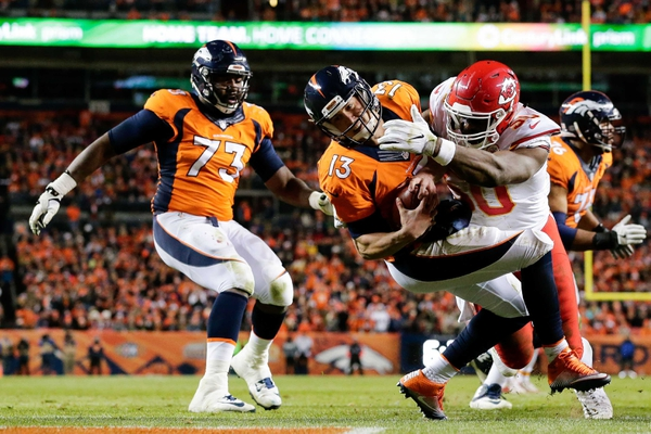 Kansas City Chiefs outside linebacker Justin Houston (50) forces a fumble against Denver Broncos quarterback Trevor Siemian (13) in the second quarter at Sports Authority Field at Mile High.