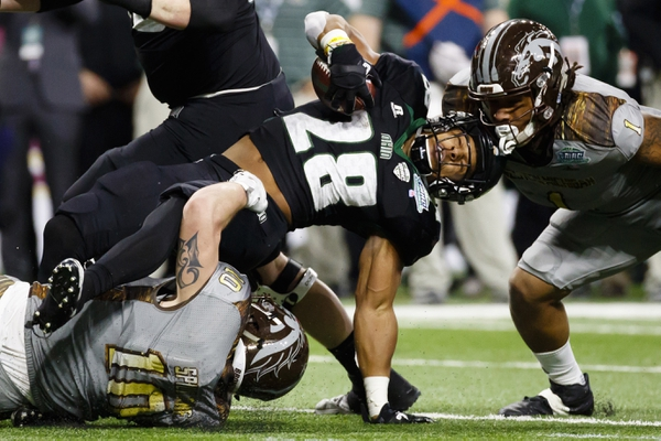 Ohio Bobcats running back Dorian Brown (28) is tackled by Western Michigan Broncos linebacker Robert Spillane (10) and defensive end Keion Adams (1) in the first half at Ford Field.