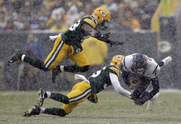 Houston Texans quarterback Brock Osweiler dives for a first down against Green Bay Packers defenders Joe Thomas and LaDarius Gunter in the first quarter at Lambeau Field.