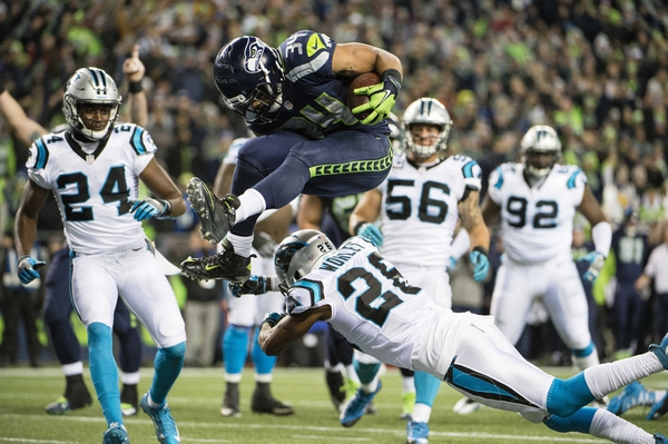 Seattle Seahawks running back Thomas Rawls (34) leaps over Carolina Panthers cornerback Daryl Worley (26) for a touchdown during the first quarter at CenturyLink Field.